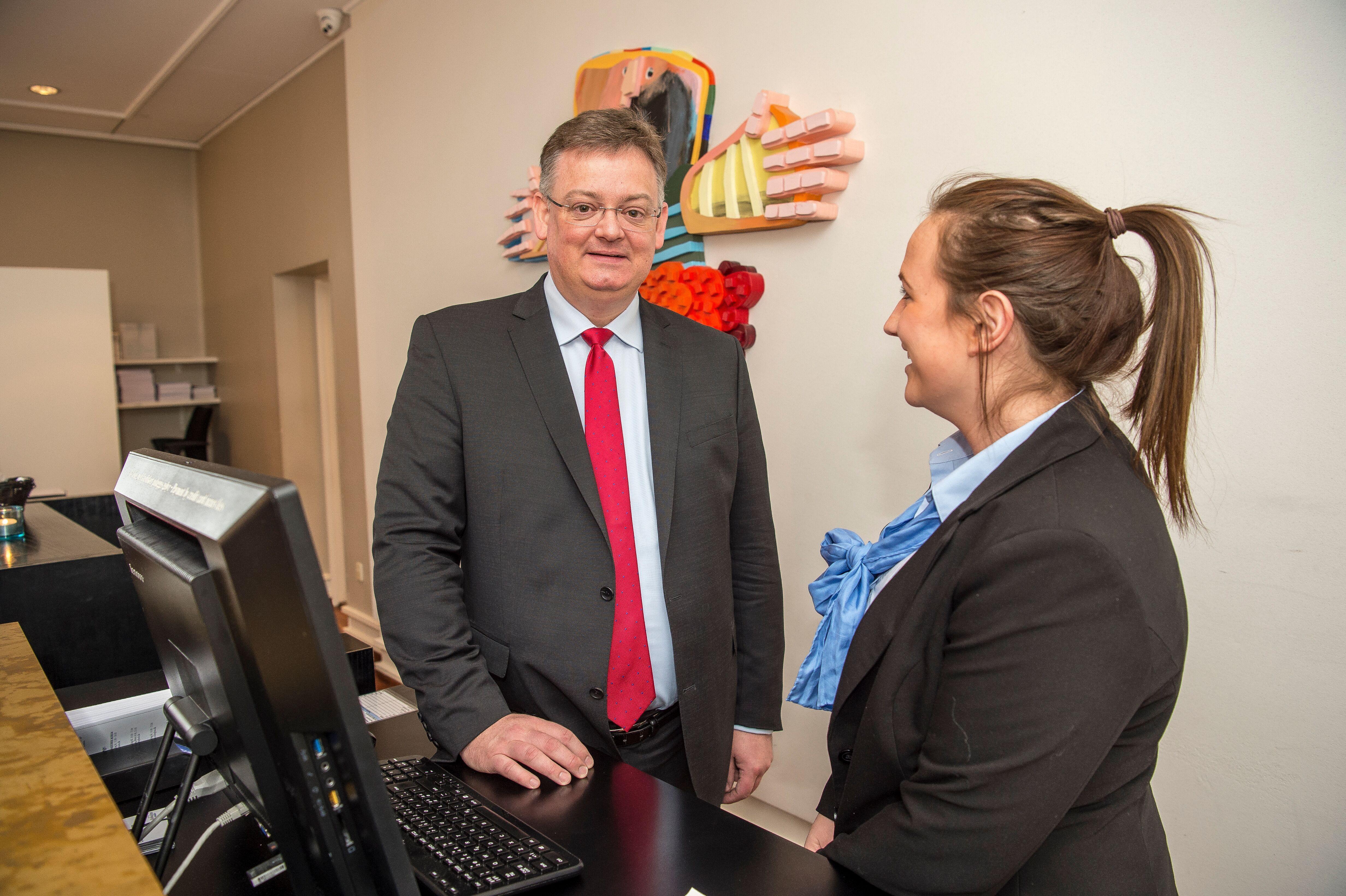 Peder J. Madsen hjælper gerne i receptionen på Hotel Koldingfjord. Her er han bag skranken med receptionist Janne Hansen.