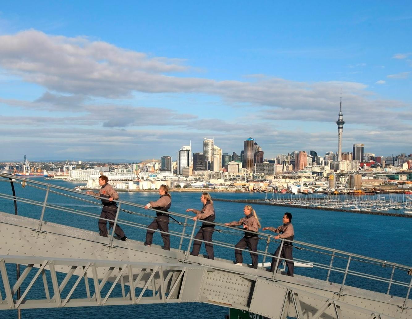 Auckland er New Zealands største by, her er en af byens store turistattraktioner i forgrunden: Auckland Bridge Climb. Foto: FDM Travel.