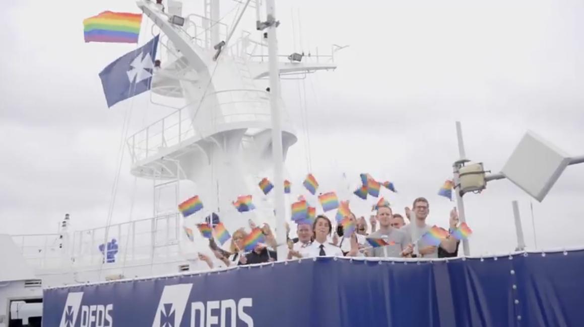 Besætningsmedlemmer fra DFDS markerer at rederiet har hejst Pride-flaget på sine to skibe mellem København og Oslo. Screendump fra DFDS-video på Facebook.