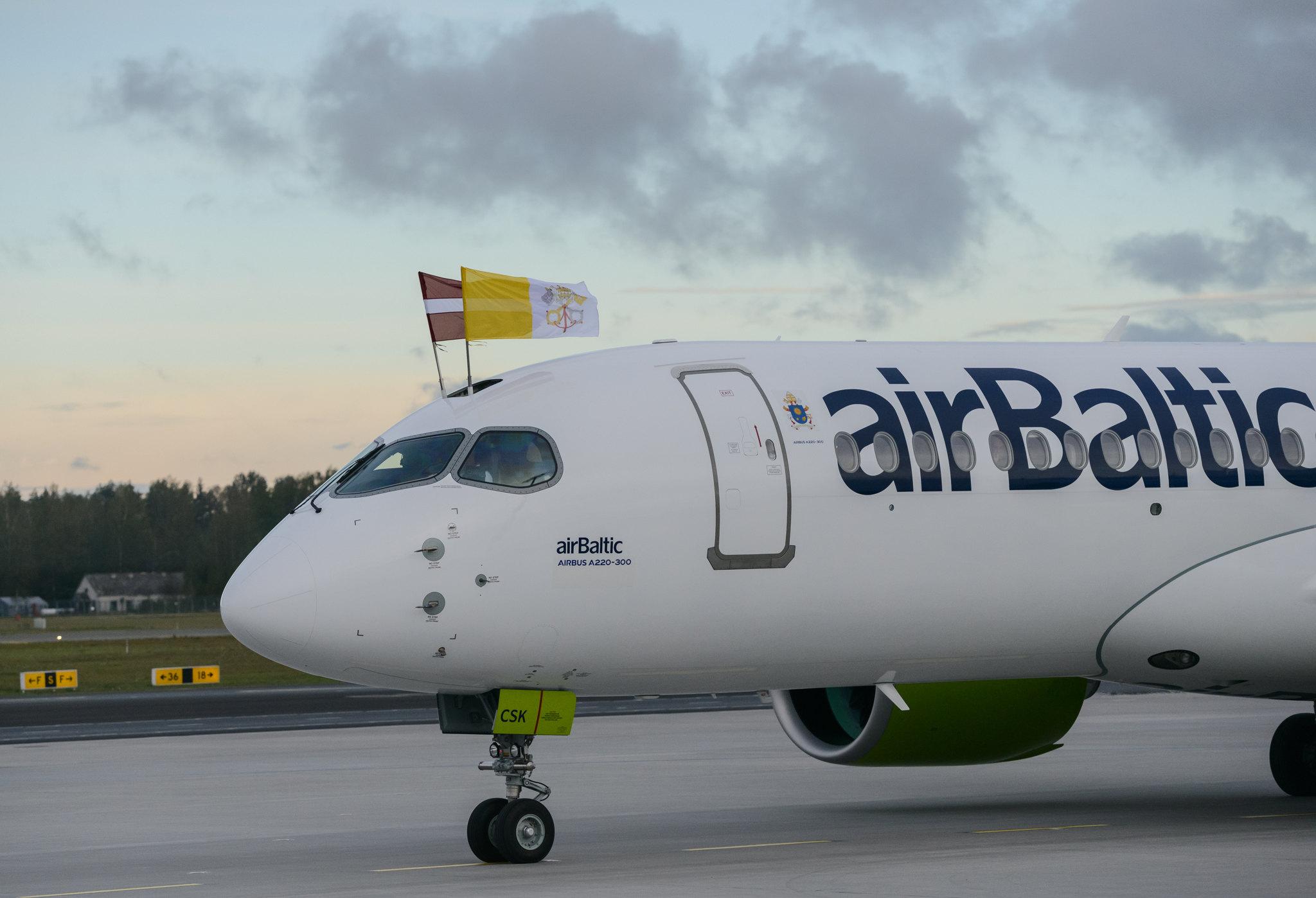 Paveflyet fra airBaltic med Vatikanstatens flag tættest på kameraet efter landingen i Riga. Pressefoto: airBaltic.