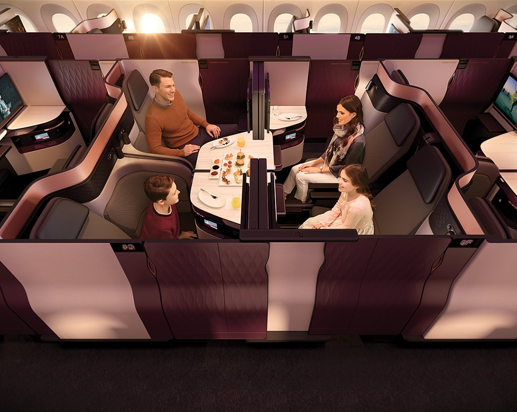"""PR-foto fra Qatar Airways med Qsuite – her ses """"dobbelt-suiten"""", hvor fire rejsende kan sidde sammen og se hinanden i passagen med bordet i midten. Pladerne mellem de to stolerækker kan skydes frem og tilbage."""