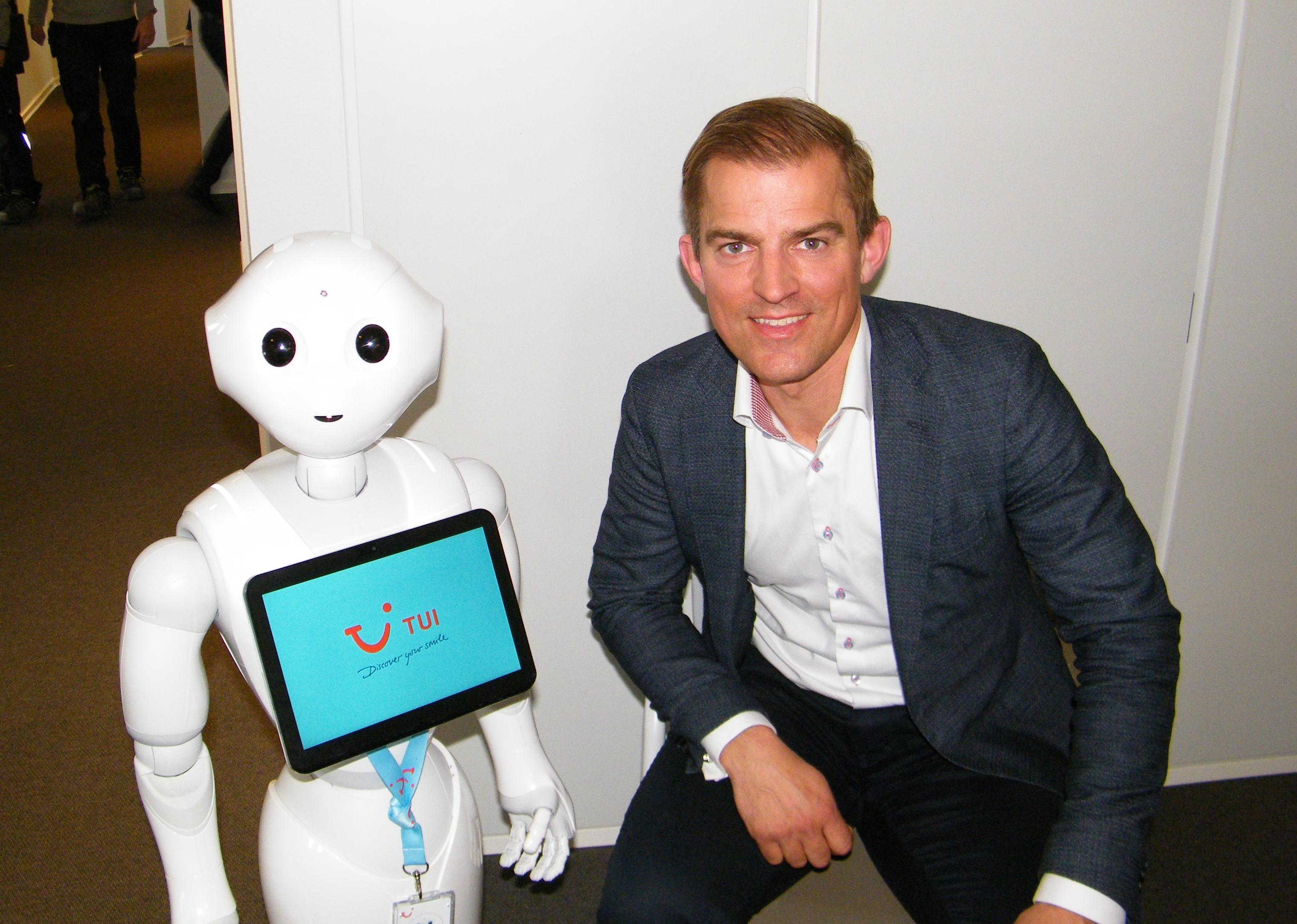 TUI's nordiske direktør, Alexander Huber, til højre, på TUI's nye danske salgskontor i København – sammen med en hjælpsom robot, der kan svare på en række spørgsmål. Foto: Henrik Baumgarten.