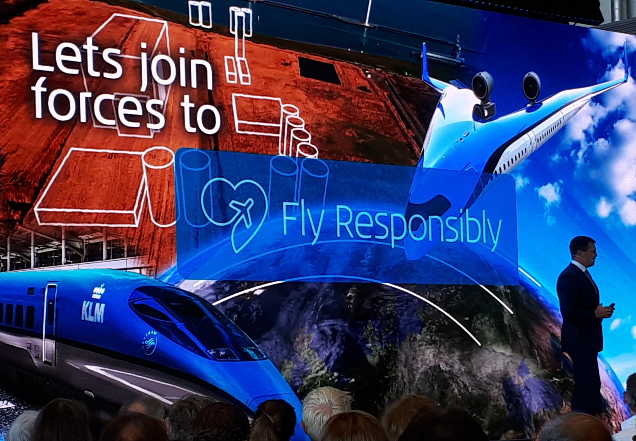 En stor kollage på storskærmen i hangaren hos KLM viste blandt andet nogle af de mange tiltag i forbindelse med flyselskabets Fly Responsibly-kampagne – bemærk KLM-toget nederst til venstre… Foto: Henrik Baumgarten.