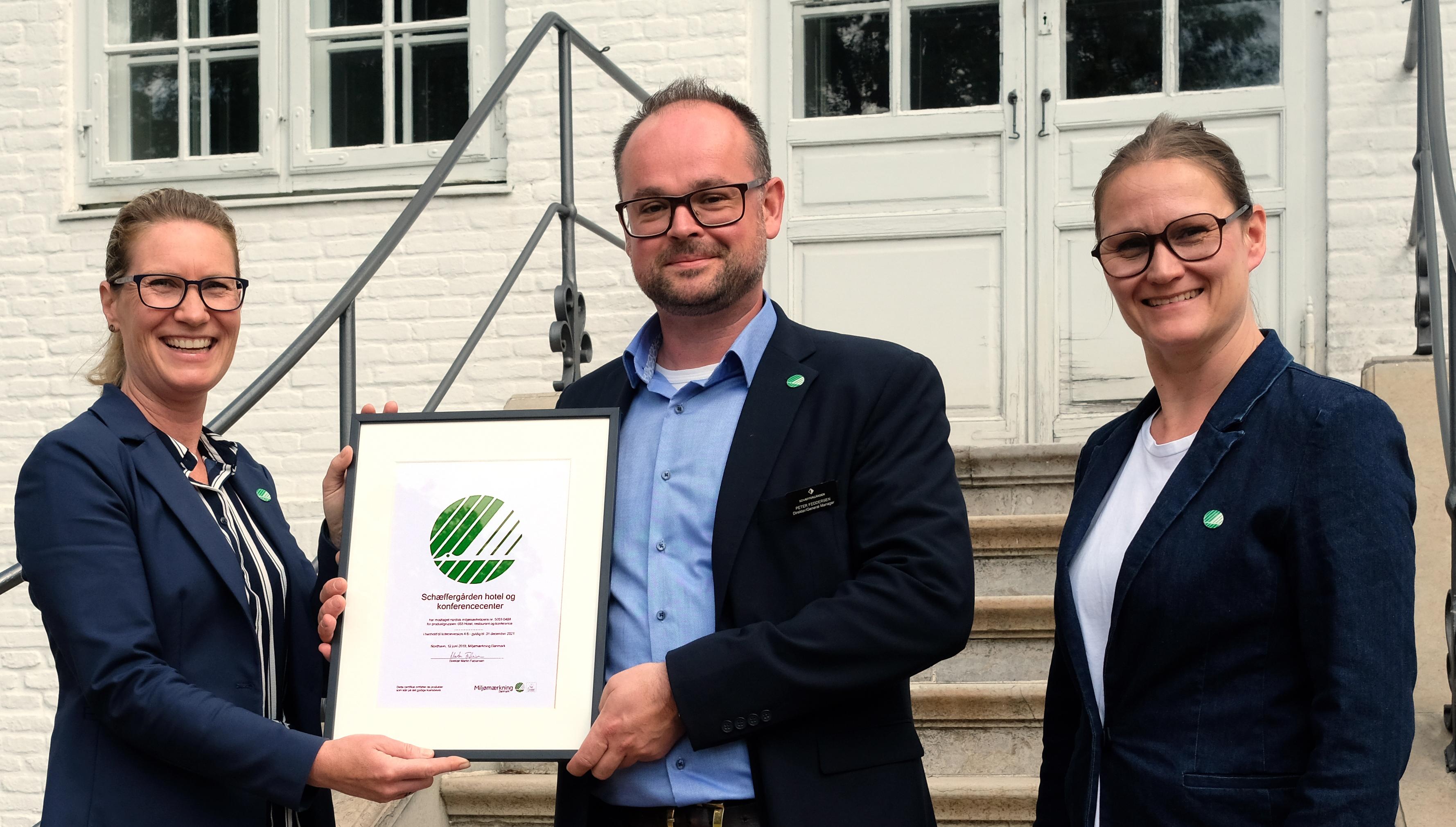 Schæffergårdens direktør, Peter Feddersen, flankeres ved den officielle overrækkelse af Svanemærke-certifikatet af konsulenter fra Miljømærkning Danmark, Ingrid Elmedal, til venstre, og Malene Nielsen. Foto: Schæffergården.