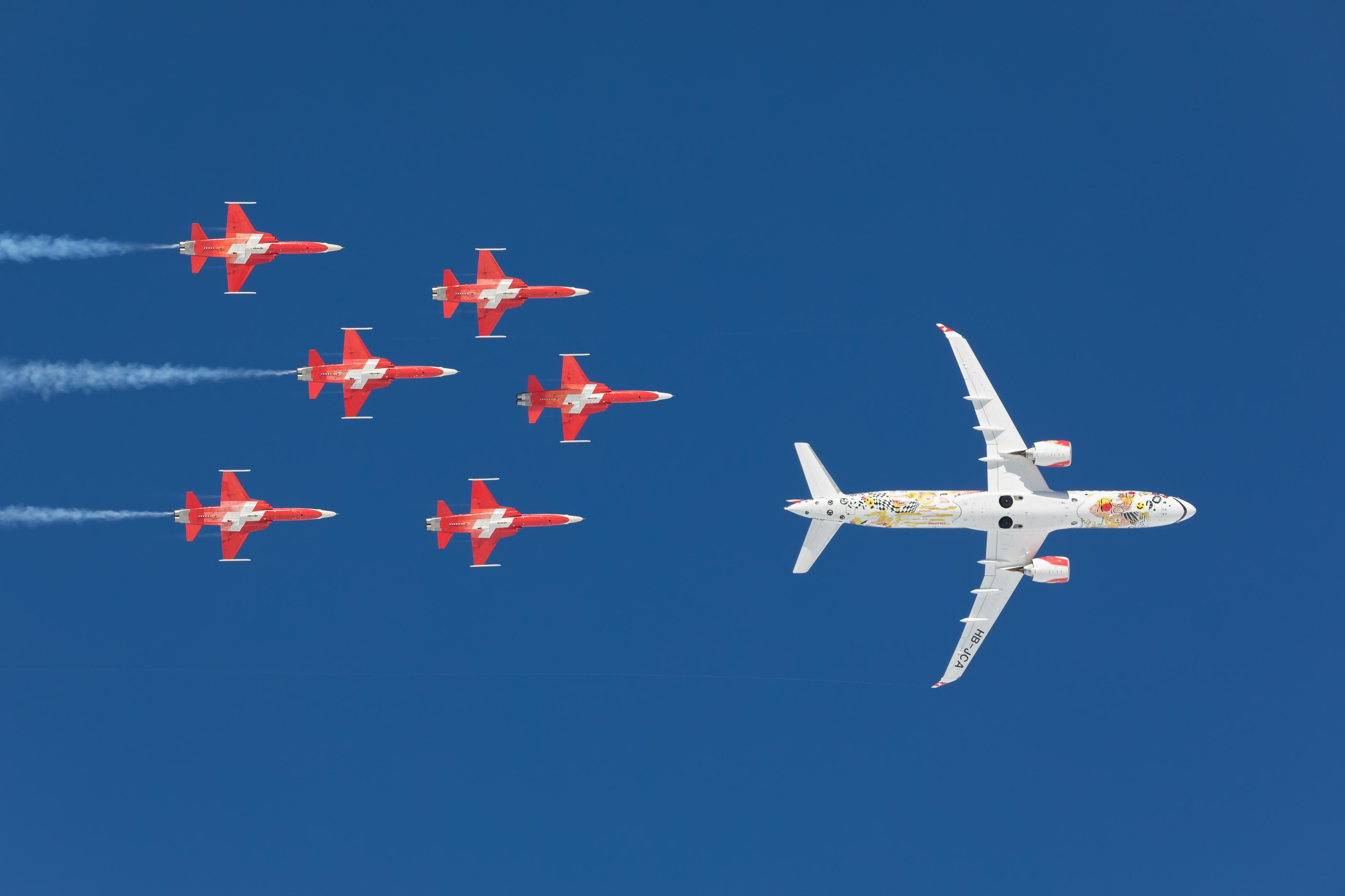 Opvisningsteamet fra det schweiziske flyvevåben Patrouille Suisse eskorterer fly fra Swiss på arkivfoto. Pressefoto: Swiss.