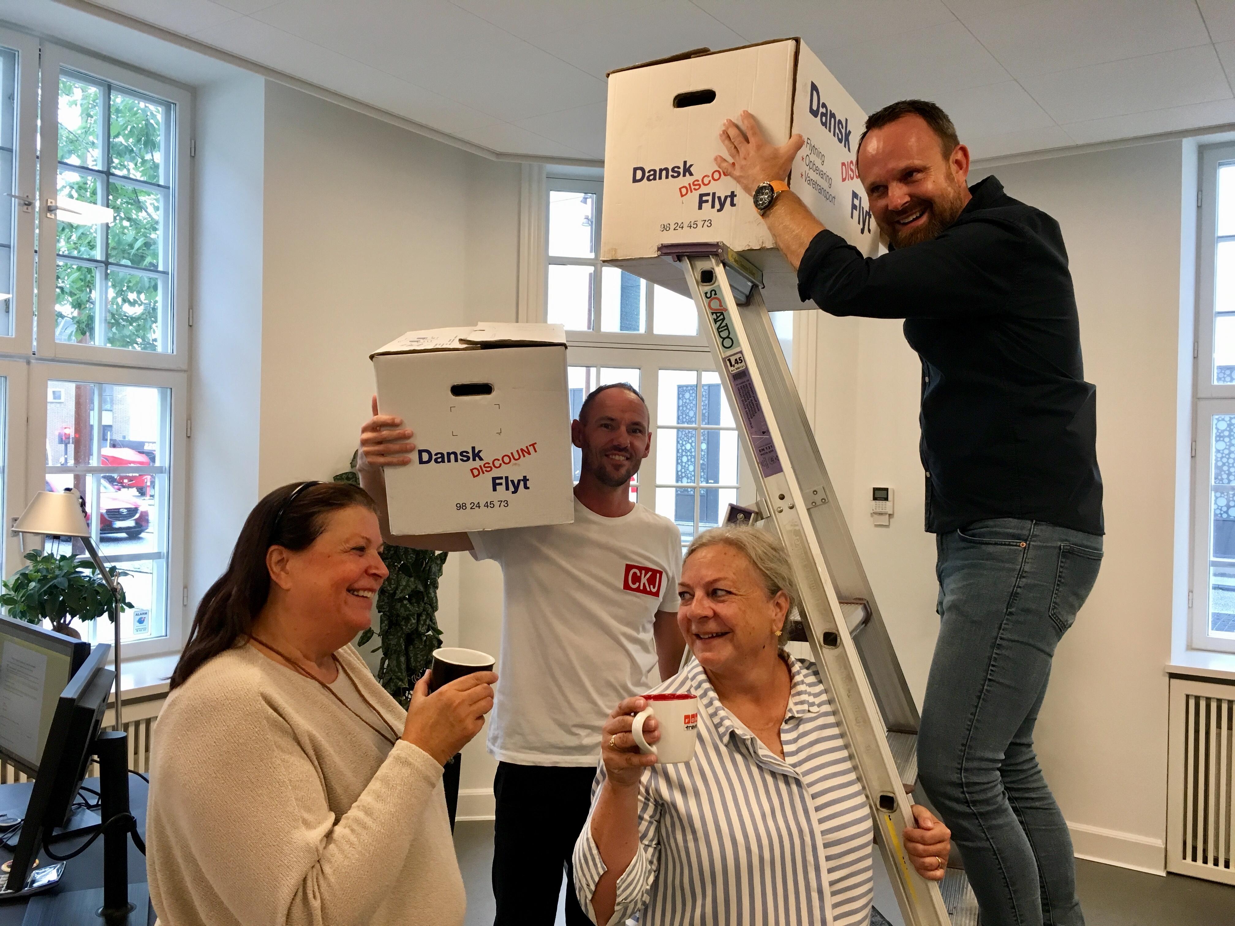 Fire af rejsespecialisterne hos FDM Travel i Aalborg pakker ud i deres nye lokaler, fra venstre Annette Holm, Stefan Fischer (supportchef), Birgit Larsen og Ruddi Joachim Andersen. Foto: FDM Travel.