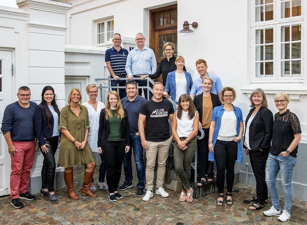 Hovedparten af medarbejderne hos Alfa Travel i Holstebro – administrerende direktør Allan Nielsen står øverst på trappen i en lyseblå skjorte. Foto: Alfa Travel.