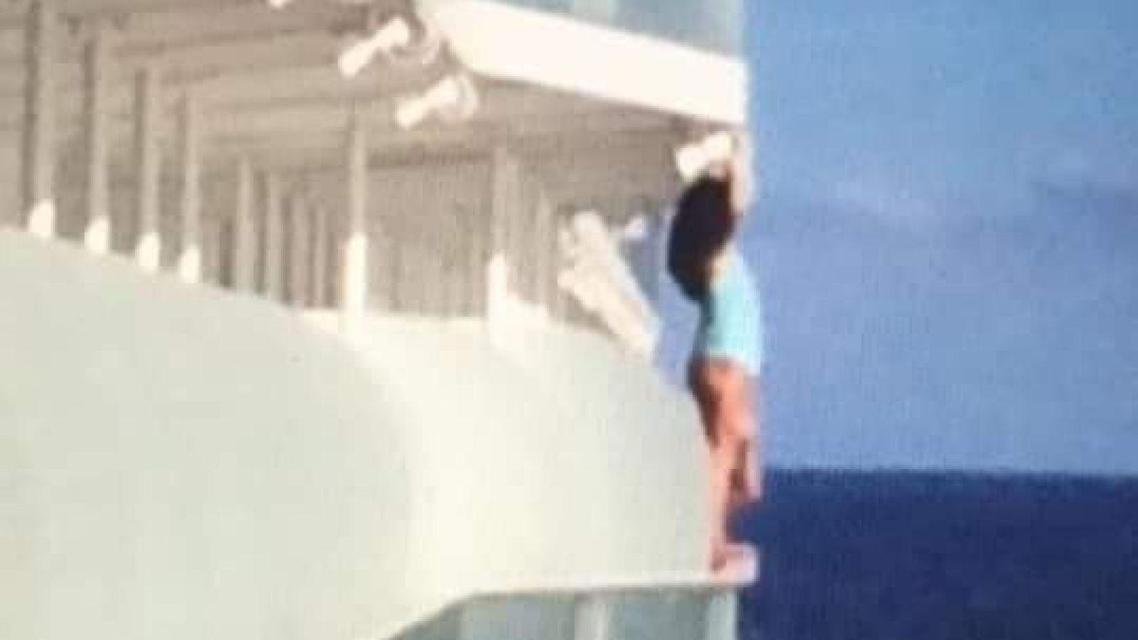 Den ikke identificerede kvinde står på kanten af krydstogtskibet Allure of the Seas – dette stunt betød, at hun og hendes medpassager blev sat i land i næste havn og for altid er forment adgang til Royal Caribbean Cruise Line. Foto via Facebook: Peter Blosic.