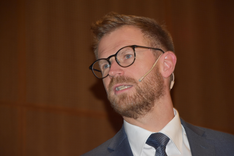 Transportminister Benny Engelbrecht under sin tale fredag ved sammenkomsten hos Danske Flyvejournalister på Clarion Hotel Copenhagen Airport, hvor han også opfordrede til øget fokus på at producere billigt bæredygtigt flybrændstof. Foto: Preben Pathuel.