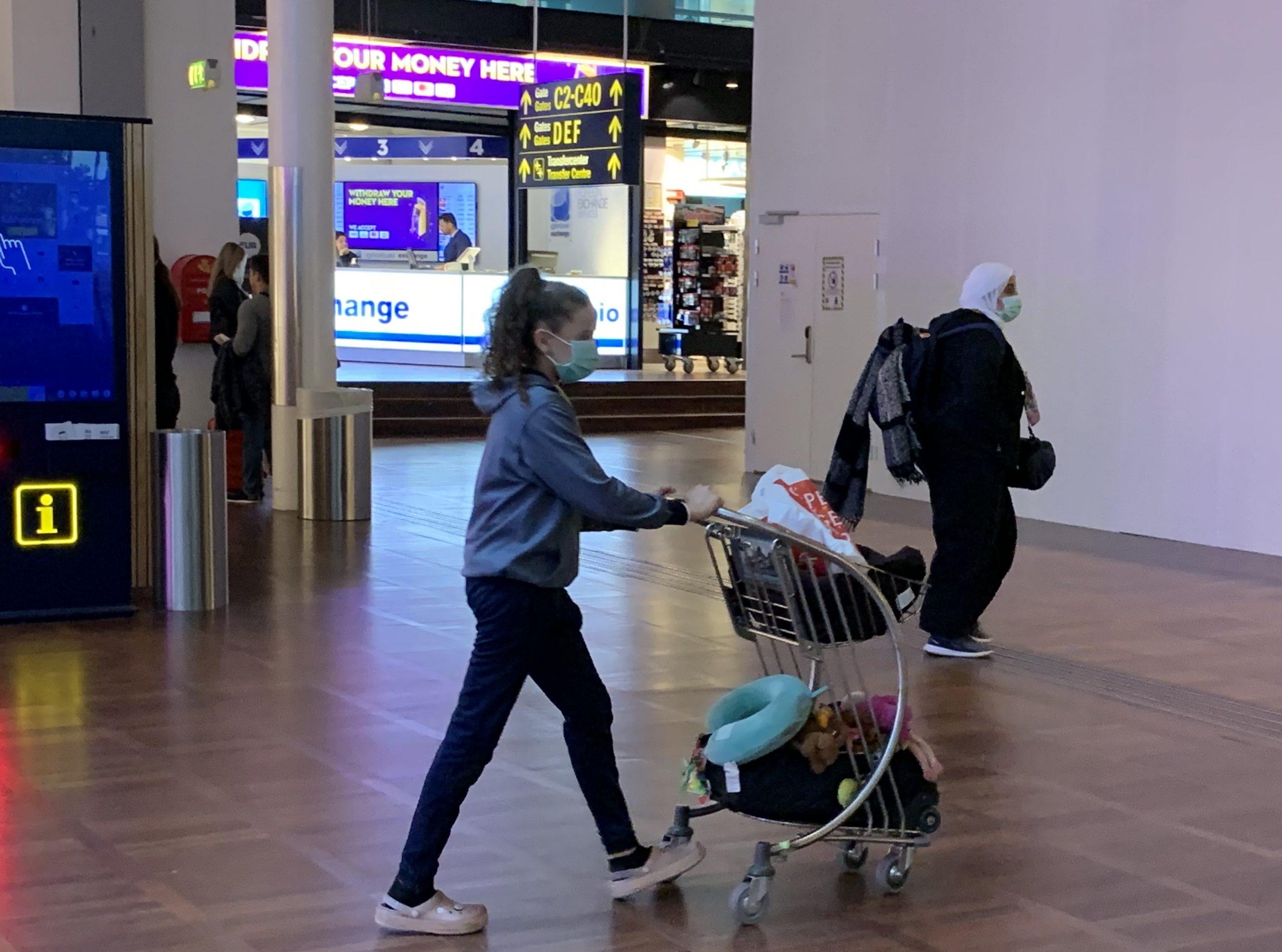 Passagerer med bind for mund og næse fotograferet i går, tirsdag, i Københavns Lufthavn. Privatfoto.
