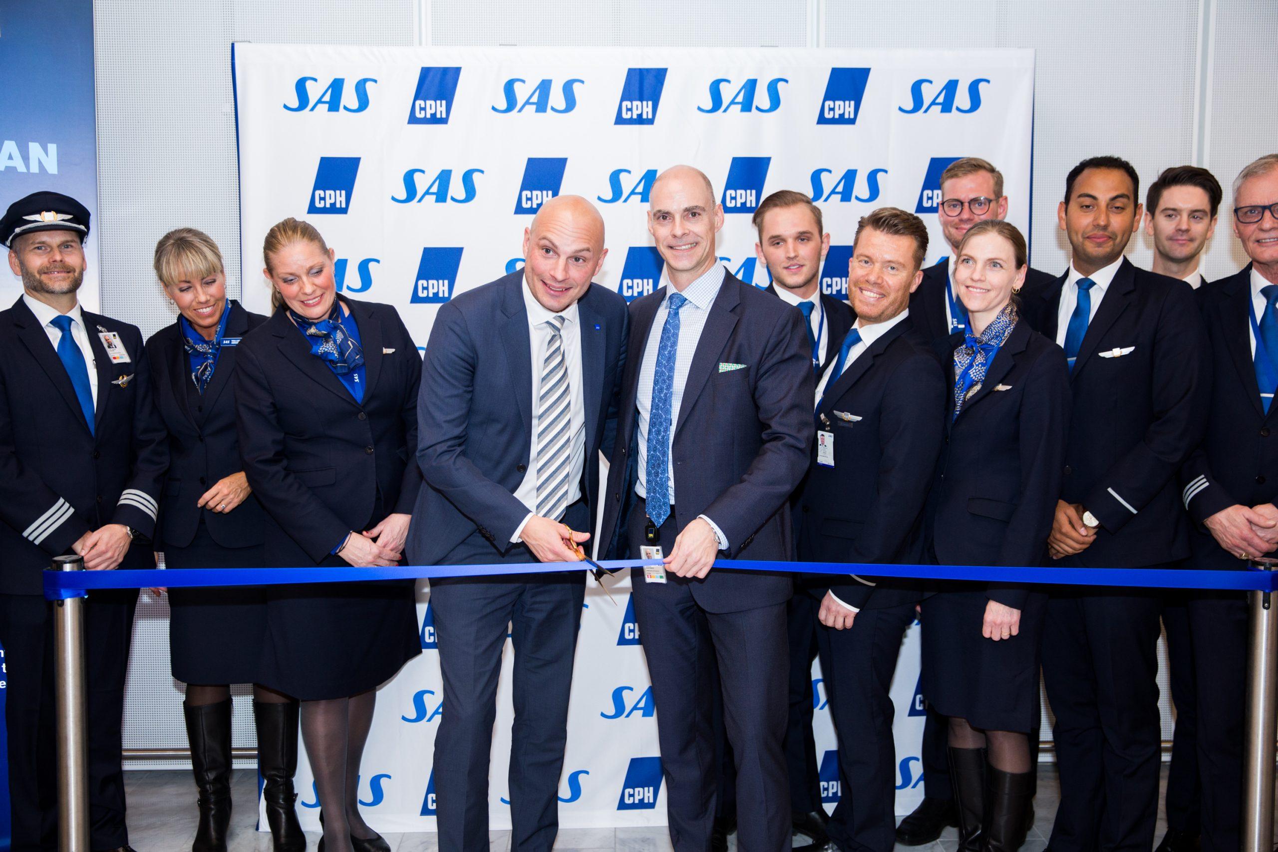 Med hovedparten af besætningen på tirsdagens SAS-afgang i baggrunden, klipper Markus Ek, SAS' globale salgsdirektør, til venstre, og Morten Tranberg Mortensen, chef for airline salg og ruteudvikling i Københavns Lufthavn, båndet der markerer første langruteflyvning med Airbus A350. Pressefoto fra SAS.