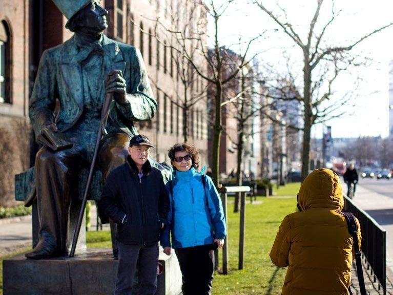 Der var sidste år 270.000 kinesiske overnatninger i Danmark, her er nogle ved H.C. Andersen-statuen ved Rådhuspladsen i København. I år forventes der færre kinesiske turister som følge af Corona-virussen. Arkivfoto.