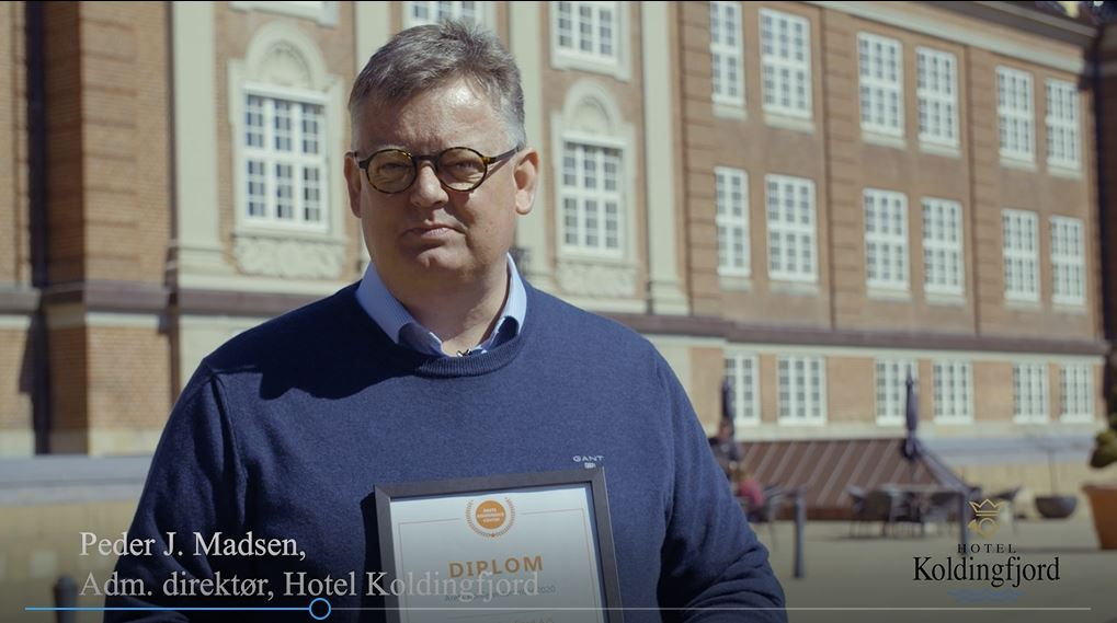 Koldingfjords direktør, Peter Madsen, foran det i øjeblikket midlertidigt lukkede hotel- og konferencecenter med beviset på at stedet har vundet prisen Årets Konferencecenter 2020. Foto: Danske Konferencecentre.