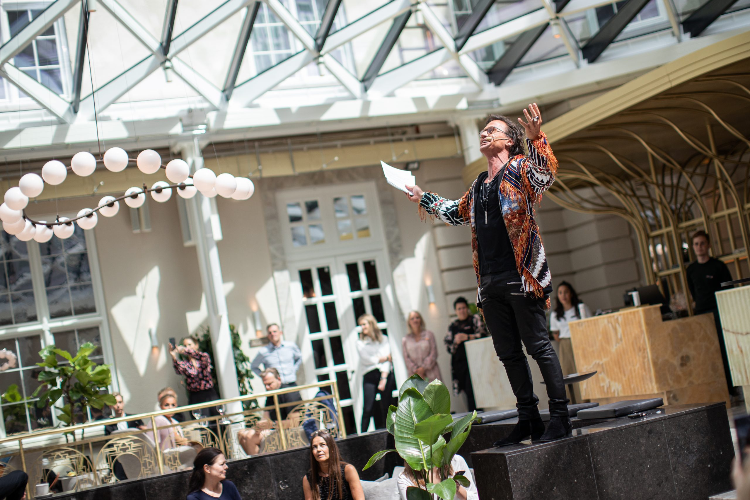 Petter Stordalen i gang med velkomsttalen i den store courtyard ved åbningen af Villa Copenhagen i onsdags. Foto for Villa Copenhagen: Astrid Rasmussen.