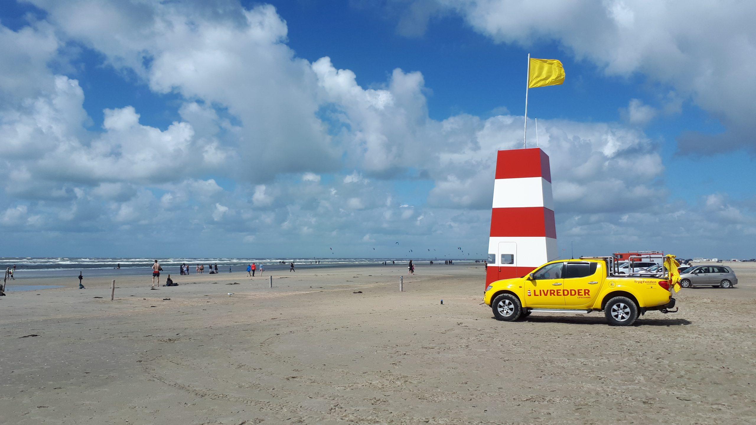 Dansk sommer på Rømø. Det gule flag ved livreddertårnet betyder fare for eksempelvis store bølger, strøm, fralandsvind, brandmænd eller særlige lokale forhold, spørg livredderen, hvis man er i tvivl. Foto: Henrik Baumgarten.