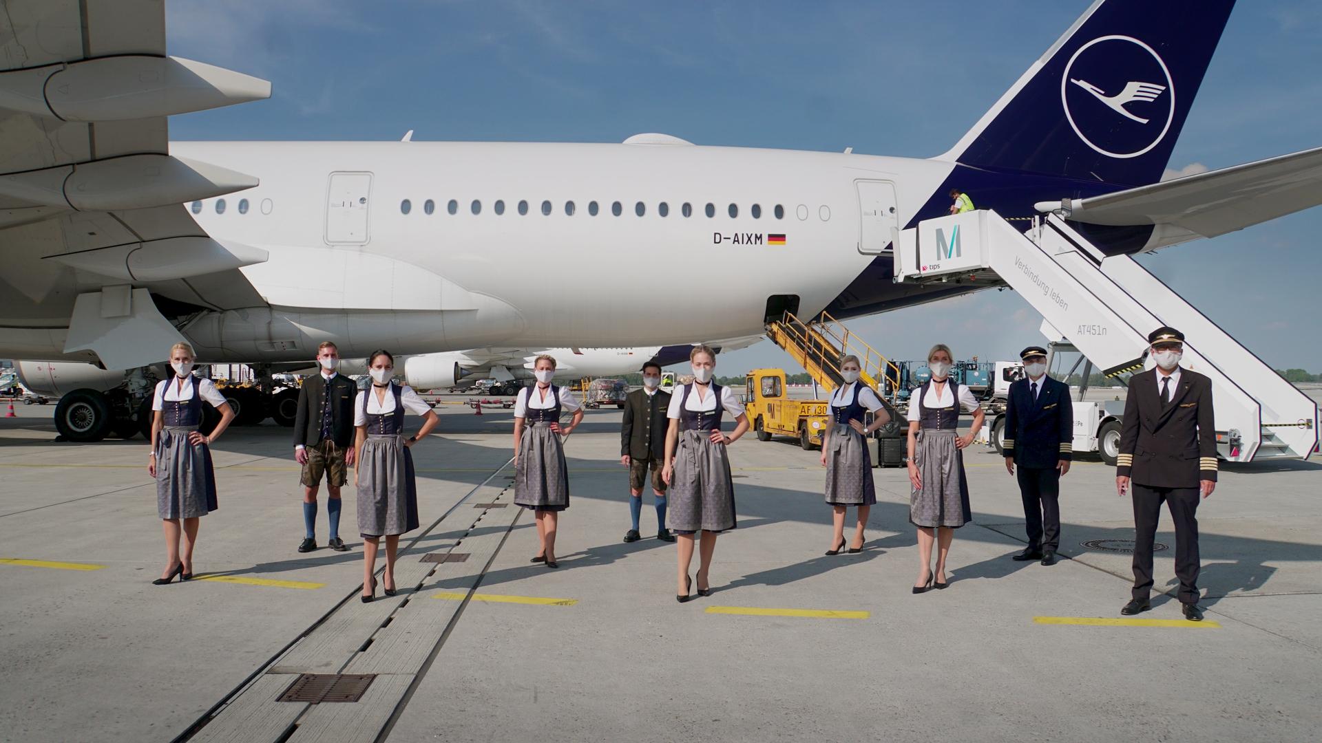 Kabinebesætning af traditionelle bayerske folkedragter foran en Airbus A350 fra Lufthansa, der blandt andet bruges på ruten mellem München og New York. Pressefoto fra Lufthansa.