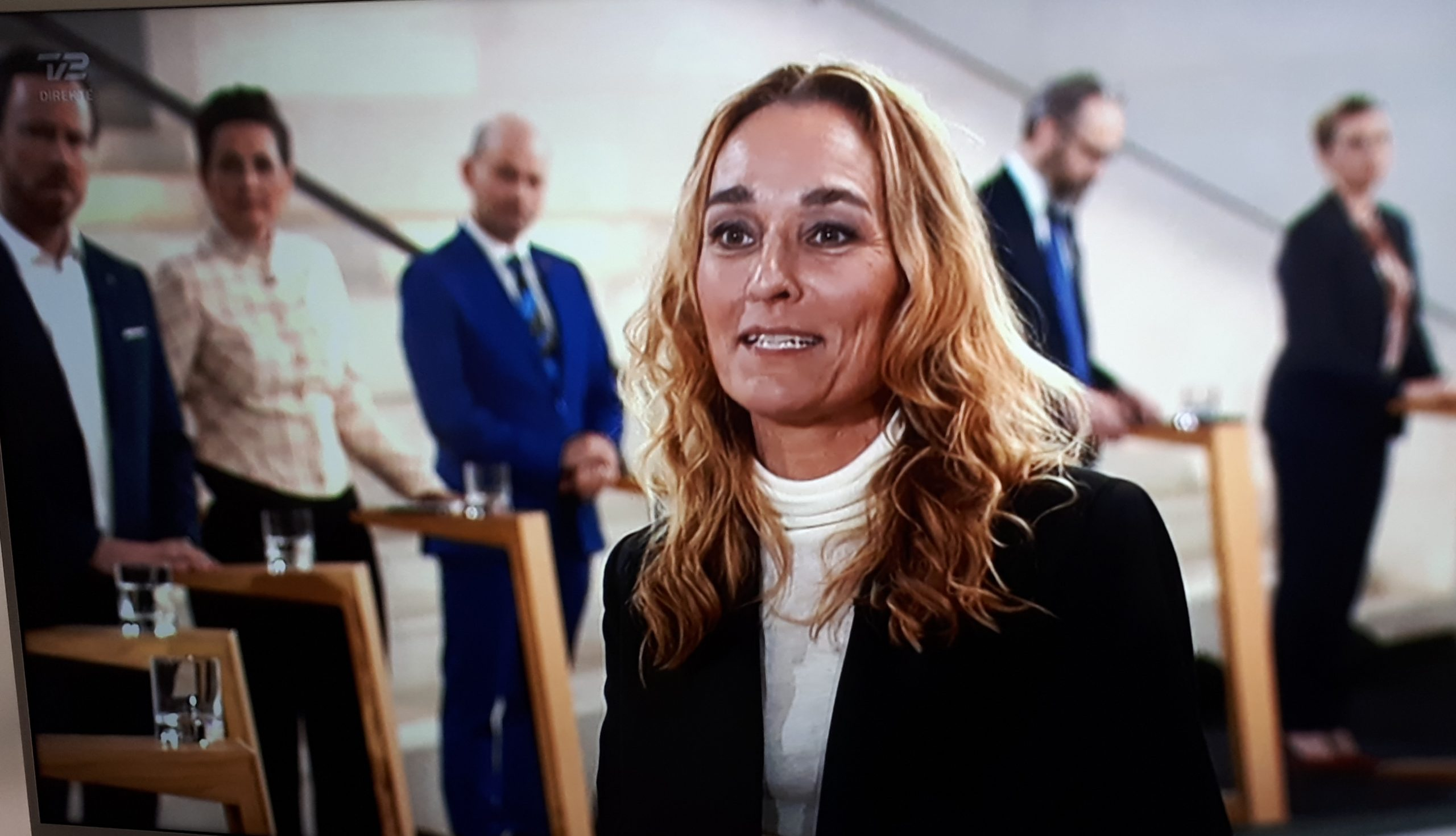 Sandra Plesner Weinert på TV 2 torsdag aften med partilederne i baggrunden, bagest til højre anes statsminister Mette Frederiksen. Screenshot fra TV 2.