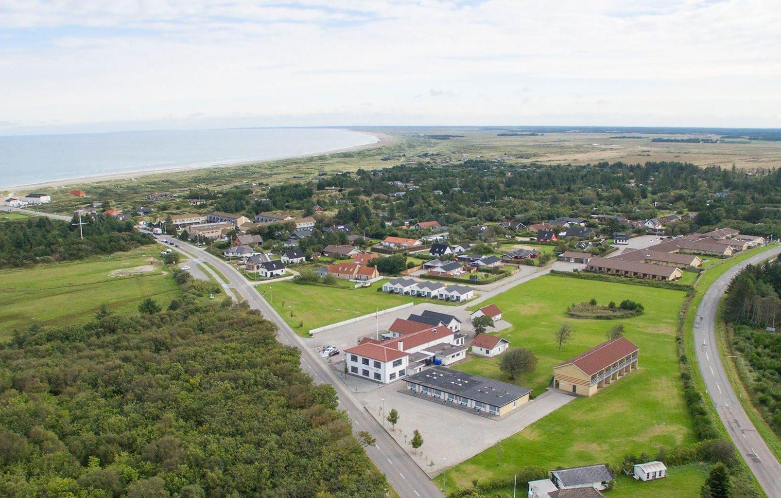 Dronefoto med Klitrosen Hotel i forgrunden, til højre ligger Rønnes Hotel og i baggrunden ses Vesterhavet. Foto: Klitrosen Hotel.