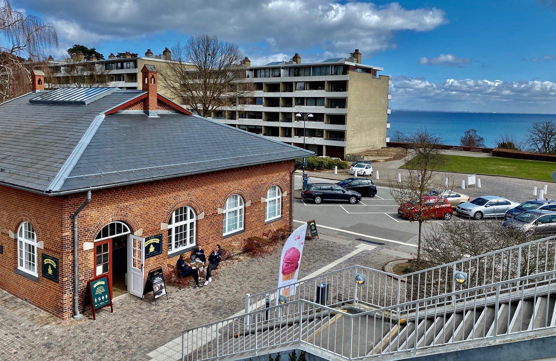 Rejsebureauet Sne og Snö og dets nye cafe har til huse i den gamle stationsbygning fra 1906 på Skodsborg Station, i forgrunden, i baggrunden ses Øresund. PR-foto: Sne og Snö.
