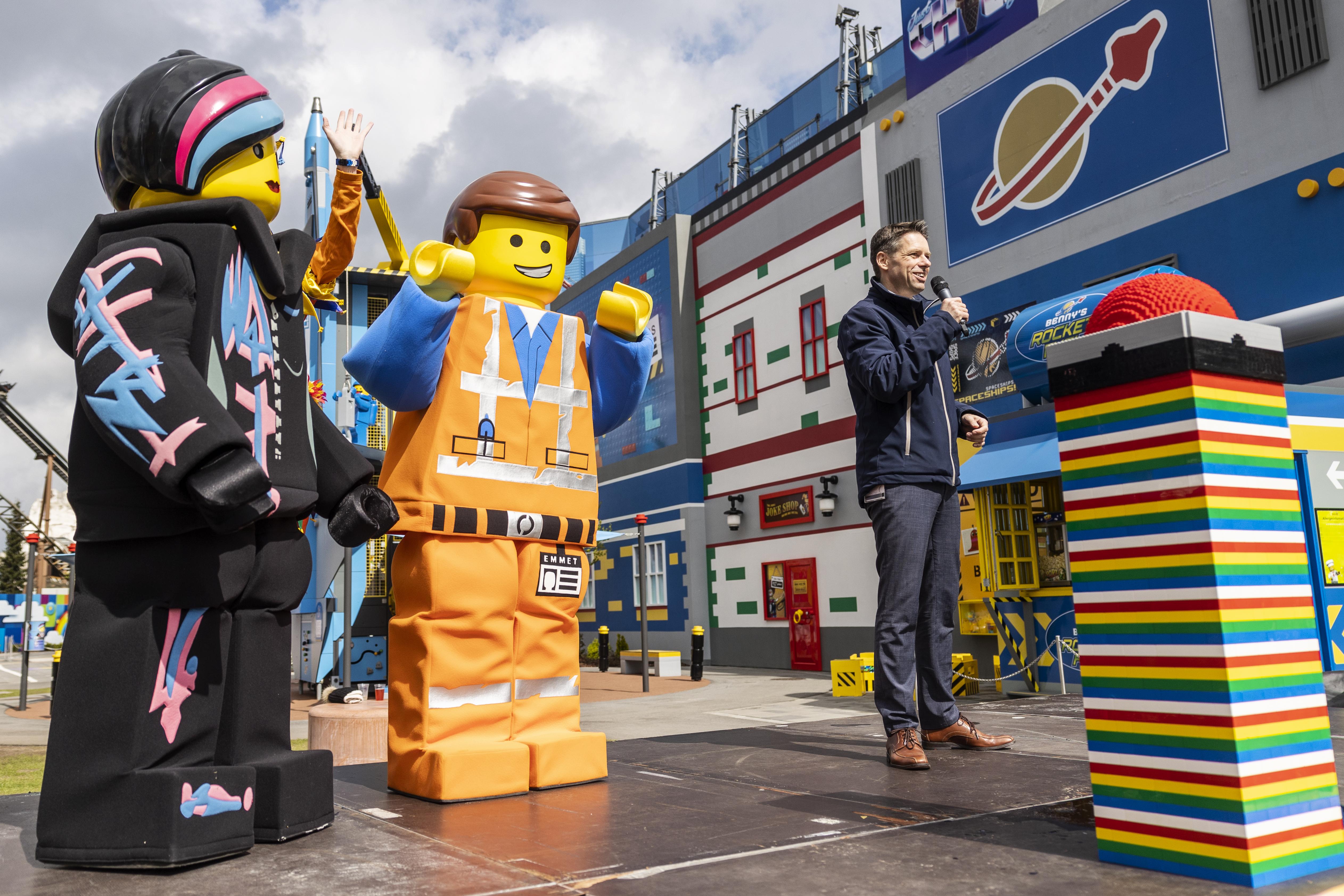 """Legolands administrerende direktør, Christian Woller, nummer tre fra venstre, taler ved sidste måneds åbning af The Lego Movie World med blandt andet Skandinaviens første """"flying theater."""" PR-foto: Legoland Billund."""