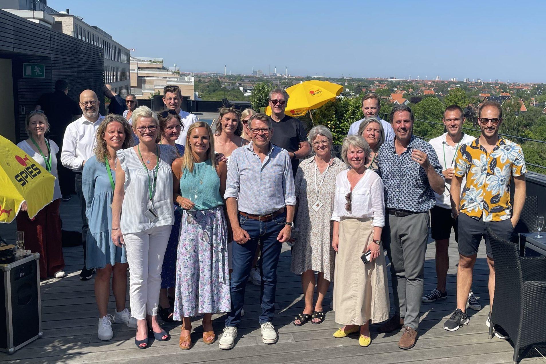 Jan Vendelbo, i midten med lyseblå skjorte, omgivet på tagterrassen i Ørestad af kolleger hos Spies ved den interne reception i forbindelse med hans 60-årsreception. Foto: Henrik Baumgarten.
